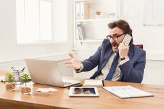 Stressed businessman with laptop talking on phone Stock Image