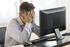 Stressed Businessman Leaning On Computer Desk Royalty Free Stock Photography
