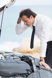 Stressed businessman looking at engine Stock Photography