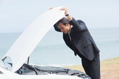 Stressed businessman looking at engine Royalty Free Stock Images