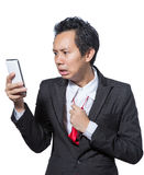 Stressed businessman looking tablet and pulling necktie Royalty Free Stock Photos