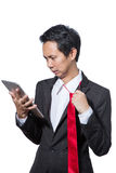 Stressed businessman looking tablet and pulling red necktie Royalty Free Stock Photography