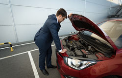 Stressed businessman looking under the car hood Royalty Free Stock Photography