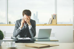 Stressed businessman on the phone. Stressed businessman talking on the phone at workplace with laptop, coffee cup and other items on desk. Blurry city view in Royalty Free Stock Images