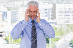 Stressed businessman rubbing his temples Royalty Free Stock Image