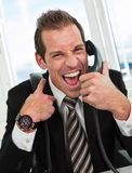 Stressed businessman screaming on the phone Stock Photos