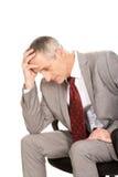 Stressed businessman sitting on armchair. Stressed mature businessman sitting on armchair Stock Photos