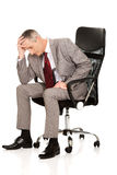 Stressed businessman sitting on armchair Royalty Free Stock Images