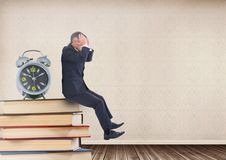 Stressed businessman sitting on Books stacked on shelf with clock. Digital composite of Stressed businessman sitting on Books stacked on shelf with clock Royalty Free Stock Images