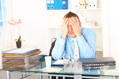 Stressed businessman sitting at desk. Holding his head and worrying Stock Photo