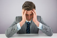 Stressed businessman sitting at desk Royalty Free Stock Photo