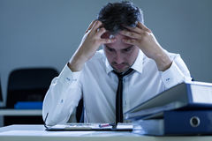 Stressed businessman sitting at desk Royalty Free Stock Photos