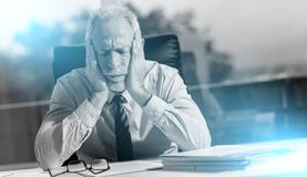 Tired businessman sitting in office, light effect stock photo