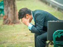 Stressed businessman sitting in park. A stressed businessman with a briefcase sitting on a bench in a park Stock Images
