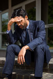 Stressed businessman sitting on steps Royalty Free Stock Photography
