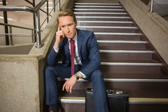 Stressed businessman sitting on steps Royalty Free Stock Photo