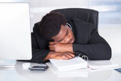 Stressed businessman sleeping in office. Portrait Of Stressed Businessman Sleeping In Office Royalty Free Stock Image