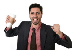 Stressed businessman in suit and tie crushing empty cup of take away coffee in caffeine addiction concept Royalty Free Stock Photography