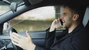 Stressed businessman swearing and talking phone while sitting inside car outdoors. Stressed young businessman swearing and talking phone while sitting inside car Stock Photo