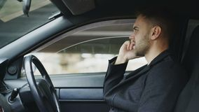 Stressed businessman swearing and talking phone while sitting inside car outdoors. Stressed young businessman swearing and talking phone while sitting inside car stock video footage