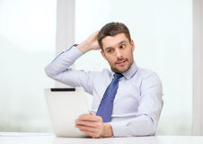 Stressed businessman with tablet pc and documents. Office, business, technology, finances and internet concept - stressed businessman with tablet pc computer and Royalty Free Stock Images