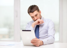 Stressed businessman with tablet pc and documents Stock Image
