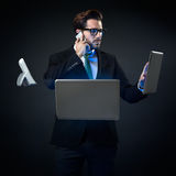 Stressed businessman talking on phone surrounded by technology. Stock Photos