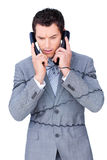 Stressed businessman tangle up in phone wires Stock Photography