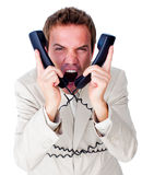Stressed businessman tangle up in phone wires. Isolated on a white background Stock Photo