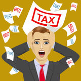 Stressed businessman with tax and bill papers shouting grabbed his head Stock Photo