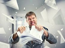 Stressed businessman tearing out stack Royalty Free Stock Photos
