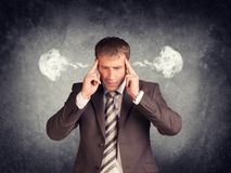 Stressed businessman thinking with his fingers on. His temples, smoke from his ears. Raw concrete wall as backdrop Royalty Free Stock Images