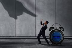 Stressed Businessman in Under Pressured Concept, Small Worker Pr. Otect an Alarm Clock with Scared posture. Shadow of Huge Pointing Hand from Terrible Boss or Stock Photo