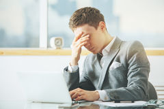 Stressed businessman using laptop Stock Images