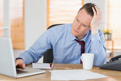 Stressed businessman working at his desk Royalty Free Stock Image