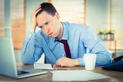 Stressed businessman working at his desk Stock Photo