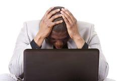 Stressed businessman working on laptop Stock Photo