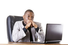 Stressed businessman working on laptop. Isolated on white Royalty Free Stock Image