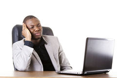 Stressed businessman working on laptop. Isolated on white Royalty Free Stock Photos