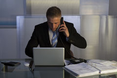 Stressed businessman working late into the night Stock Photos