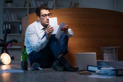 The stressed businessman working overtime in depression. Stressed businessman working overtime in depression Stock Image