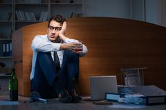 The stressed businessman working overtime in depression. Stressed businessman working overtime in depression Royalty Free Stock Photos