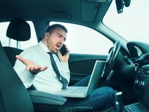 Stressed businessman working seated in car. Stressed businessman working seated in his car Royalty Free Stock Photos