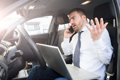 Stressed businessman working seated in car Stock Images