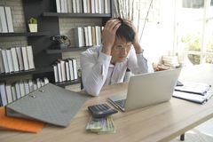 Stressed businessman working under pressure in the office stock image