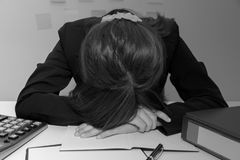 Stressed businesswoman bend down the head  or sleep at her desk,. Overwork, black and white concept Stock Image