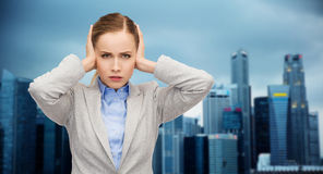 Stressed businesswoman with covered ears Stock Photo