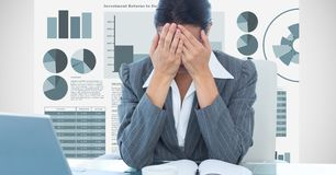 Stressed businesswoman covering face with hands against graphs. Digital composite of Stressed businesswoman covering face with hands against graphs Stock Image