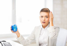 Stressed businesswoman holding clock Royalty Free Stock Photos