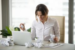 Stressed businesswoman holding crumpled paper trying to finish u. Frustrated stressed businesswoman holding crumpled paper looking at laptop trying to finish royalty free stock image